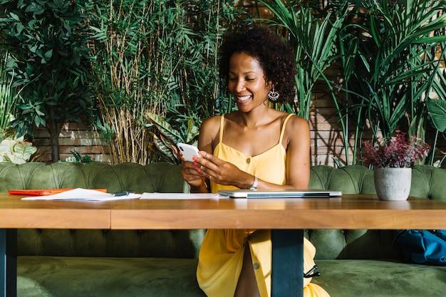 Stilvolle junge frau, die im restaurant unter verwendung des smartphone sitzt