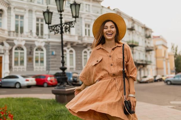 Stilvolle junge frau, die in europa reist, gekleidet im frühling trendiges kleid, hut, tasche und accessoires