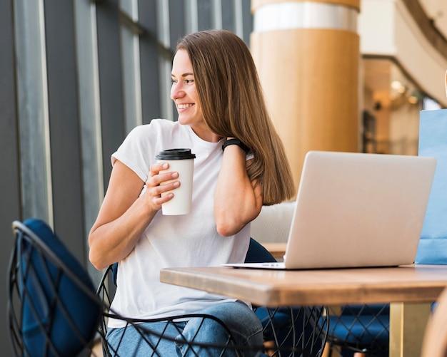 Stilvolle junge frau, die kaffeetasse hält