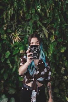 Stilvolle junge frau, die mit altmodischer kamera fotografiert