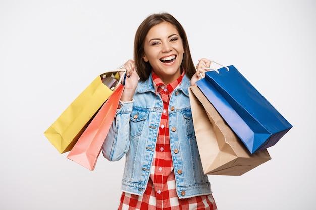 Stilvolle junge frau, die mit einkaufstaschen nach großartigem einkauf aufwirft