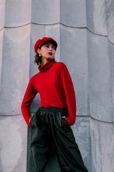 Stilvolle junge frau, die rote kappe mit den händen in ihrer tasche weg schaut trägt