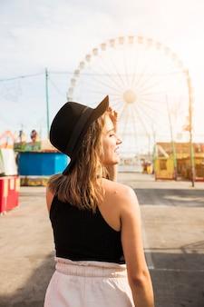 Stilvolle junge frau, die schwarzen hut auf ihrem kopf steht am vergnügungspark trägt