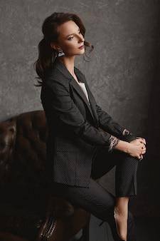 Stilvolle junge frau ein büroangestellter in einem stylischen anzug und weißer bluse posiert auf dem vintage-sessel
