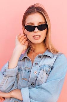 Stilvolle junge frau im blauen denimhemd, das gegen rosa hintergrund steht