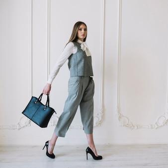 Stilvolle junge frau im kostüm mit handtasche im raum