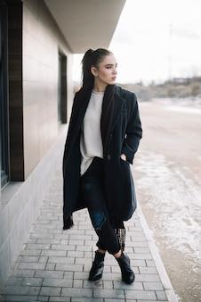 Stilvolle junge frau im mantel mit schal auf der straße
