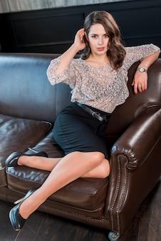 Stilvolle junge frau in den schwarzen hohen absätzen, die auf braunem sofa sitzen