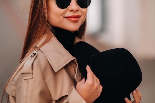 Stilvolle junge frau in einem beigen mantel und einem schwarzen hut in seinen händen und in der brille auf einer stadtstraße. straßenmode für frauen. herbstkleidung. urbaner stil.