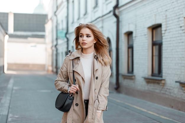 Stilvolle junge frau in einem frühlingslichtmantel in einem weißen t-shirt mit einer stilvollen schwarzen lederhandtasche, die die straße entlang vor dem hintergrund eines alten backsteingebäudes geht. modisches süßes europäisches mädchen