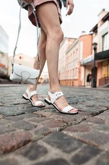 Stilvolle junge frau in einem modischen rosa rock in vintage-sandalen mit einer weißen tasche posiert auf einer steinstraße