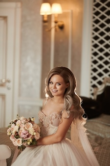 Stilvolle junge frau in einem schönen weiblichen modell des hochzeitskleides mit brautmake-up und -frisur in einem ...