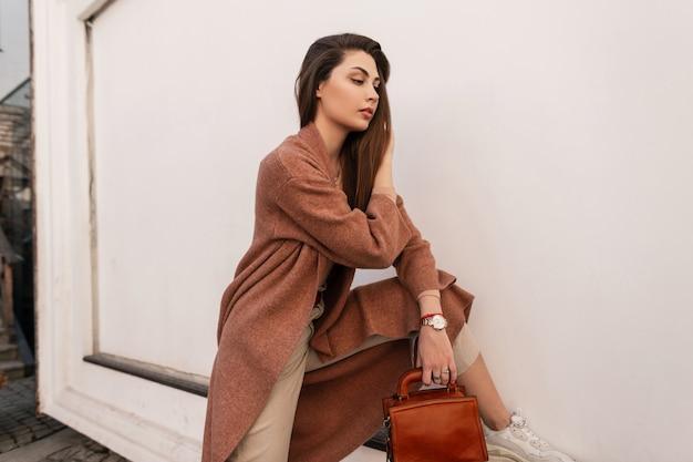 Stilvolle junge frau in modischem mantel in modischer beiger hose mit brauner lederhandtasche im schuh glättet langes haar in der nähe der vintage-wand in der stadt. modellaufstellung des recht eleganten mädchens. frühlingsstil.