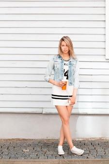 Stilvolle junge frau in modischer sommerkleidung in stilvollen weißen turnschuhen, die nahe an einer holzwand draußen an einem warmen sommertag aufwerfen. schönes mädchen trinkt heißen kaffee. tolles wochenende.