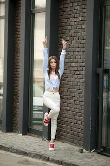 Stilvolle junge frau in weißen jeans geht und springt auf stadtstraßen gegen backsteinmauer