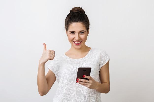 Stilvolle junge frau mit attraktivem gesicht, das smartphone hält und daumen hoch zeigt, positive geste, lächeln, gute laune, unter verwendung des mobilen geräts, isoliert