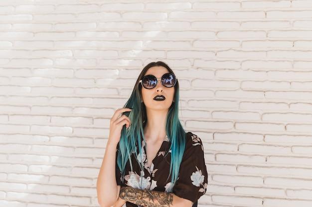 Stilvolle junge frau mit dem gefärbten haar, das vor beige wand steht