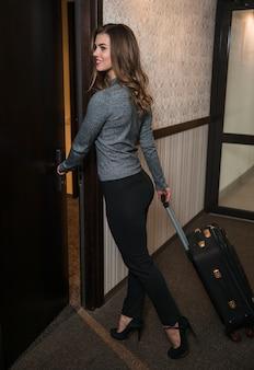 Stilvolle junge frau mit der gepäcktasche, welche die tür im hotel öffnet