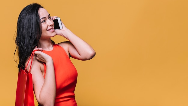 Stilvolle junge frau mit der tasche, die am telefon plaudert