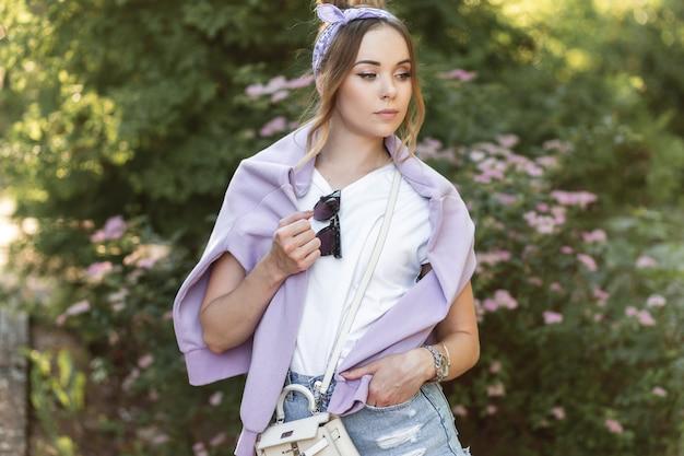 Stilvolle junge frau mit einem bandana in einem weißen t-shirt mit einem lila sweatshirt und blauen jeansshorts steht in der nähe von blumen im freien