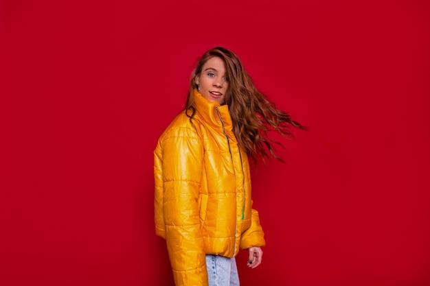 Stilvolle junge frau mit fliegendem langem gewelltem haar, das gelbe jacke trägt, die über rote wand aufwirft