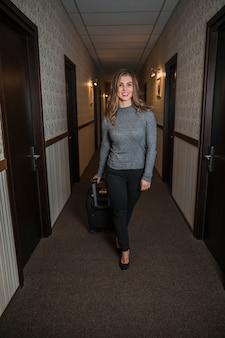 Stilvolle junge frau mit gepäcktasche gehend in den hotelkorridor