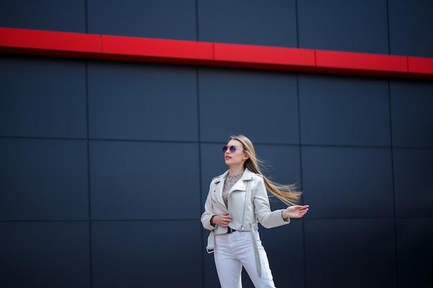 Stilvolle junge frau mit langen blonden haaren europäischen aussehens mit einem lächeln im gesicht. mädchen in weißer jacke und weißer jeans an einem warmen sonnigen sommertag auf dem hintergrund eines grauen gebäudes