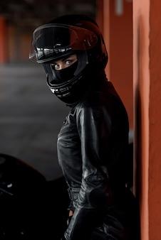 Stilvolle junge frau motorradfahrerin mit schönen augen in schwarzer schutzausrüstung und integralhelm in der nähe ihres fahrrads auf tiefgarage. extremal- und freiheitskonzept.