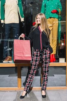 Stilvolle junge frau, welche die einkaufstaschen stehen vor fensteranzeige hält