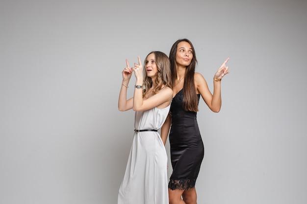 Stilvolle junge frauen, die abendkleider tragen, die auf leerzeichen für ihren inhalt auf grauem studiohintergrund zeigen