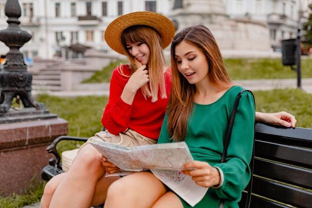 Stilvolle junge frauen, die zusammen in europa reisen, gekleidet im trendigen frühlingsoutfit und in den accessoires