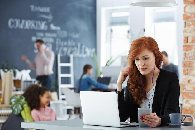 Stilvolle junge geschäftsfrau, die an ihrem laptop im modernen büro arbeitet