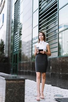 Stilvolle junge geschäftsfrau, die mitnehmerkaffeetasse und smartphone stehen vor bürogebäude hält
