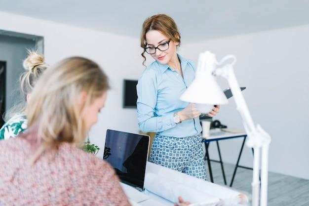 Stilvolle junge geschäftsfrau, die weibliches arbeiten zwei am arbeitsplatz betrachtet