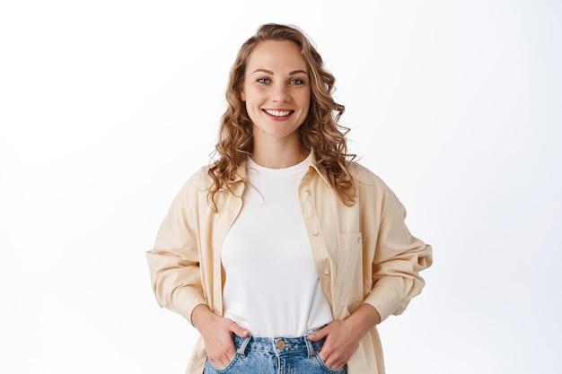 Stilvolle junge moderne frau mit blonder frisur, händchen haltend in jeanstaschen und unbeschwert lächeln, selbstbewusst und entschlossen aussehend, weiße wand