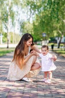 Stilvolle junge mutter, die mit ihrer kleinen tochter im stadtpark geht.