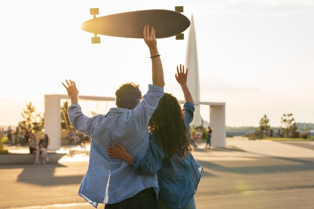 Stilvolle junge paarumarmung mit blick auf den sonnenuntergang halten skateboard glückliches mädchen und verliebter kerl genießen freiheit