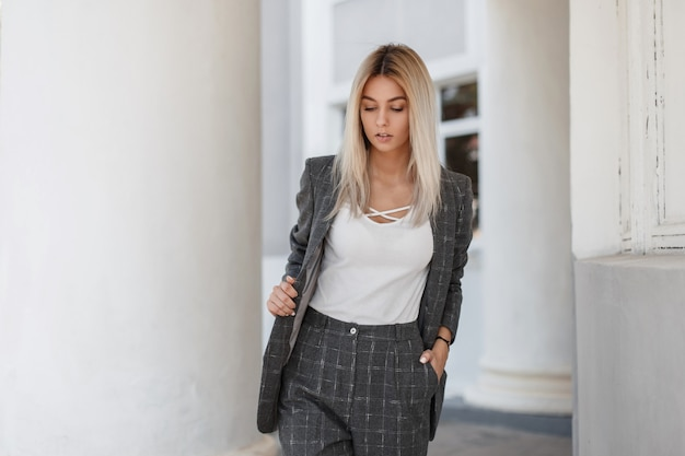 Stilvolle junge schöne frau in einem mode-weinlese-grauen anzug, der auf der straße geht
