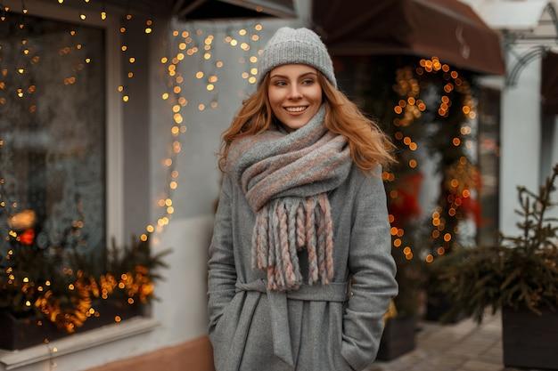 Stilvolle junge schöne frau mit einem lächeln in modischer strickkleidung mit einem stilvollen vintage-hut mit einem schal in der stadt nahe den girlanden und den gelben lichtern