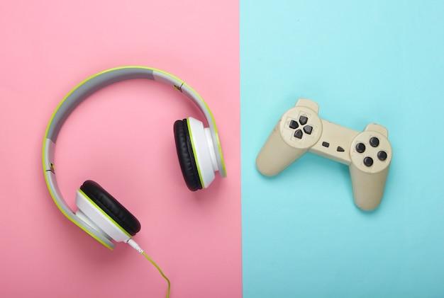 Stilvolle kabelgebundene stereo-kopfhörer mit gamepad auf rosa und blauer oberfläche