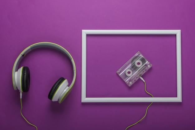 Stilvolle kabelgebundene stereokopfhörer mit audiokassette auf lila oberfläche mit weißem rahmen