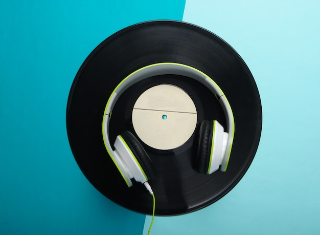 Stilvolle kabelgebundene stereokopfhörer mit schallplatte auf blauer oberfläche
