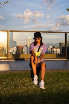 Stilvolle kaukasische frau in der trendigen neutasche panama und taille auf dach in bangkok mit ansicht