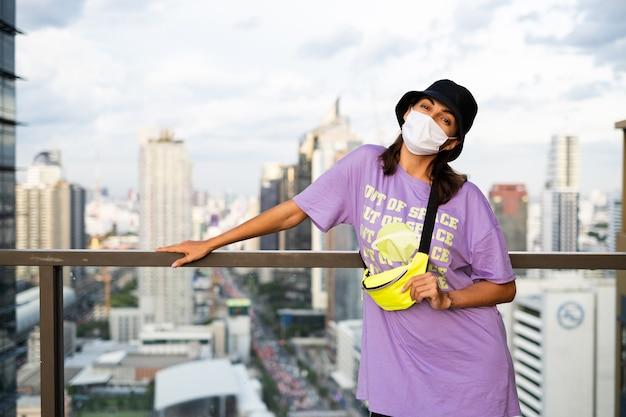 Stilvolle kaukasische frau in der trendigen neutasche panama und taille auf dach in bangkok.
