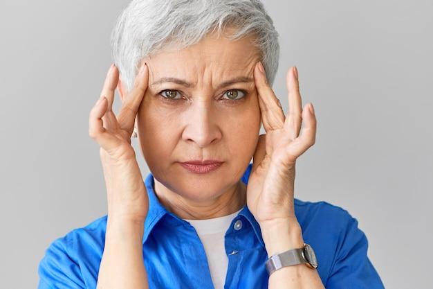 Stilvolle kaukasische frau mittleren alters im blauen hemd, das unter migräne leidet. nahaufnahme der gestressten reifen frau, die wegen schrecklicher kopfschmerzen ihre schläfen drückt und schmerzhafte punkte massiert