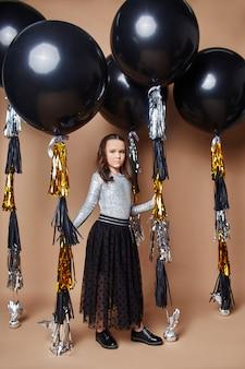 Stilvolle kinder in abendkleidern und kostümen feiern den ersten schultag.