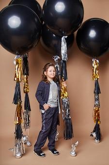 Stilvolle kinder in abendkleidern und kostümen feiern den ersten schultag