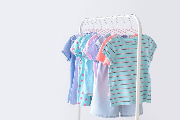 Stilvolle kinderkleidung, die auf gestell gegen helle oberfläche hängt