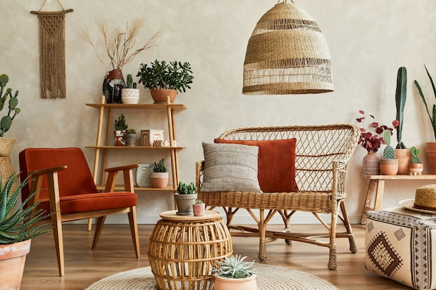 Stilvolle komposition aus gemütlichem wohnzimmer mit kopienraum, vielen pflanzen, holzregalen, rattansofa und boho-accessoires. beige wand, teppich auf dem boden. pflanzen lieben konzept. vorlage.