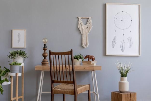 Stilvolle komposition aus kreativem, geräumigem arbeitsbereich mit rahmen, holztisch und stuhl, pflanzen und accessoires. graue wände und parkettboden. boho-stil.